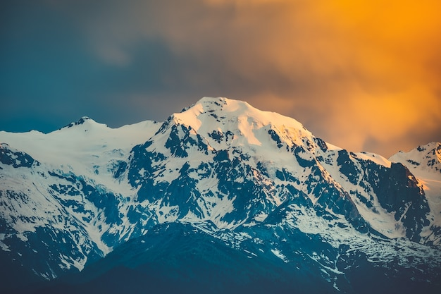 Schöner sonnenuntergang über dem schneebedeckten berggipfel. naturlandschaftsszene. reise-hintergrund. urlaub, reisen, sport, erholung. kaukasischer hauptkamm, swanetien, georgien. retro-tonungsfilter