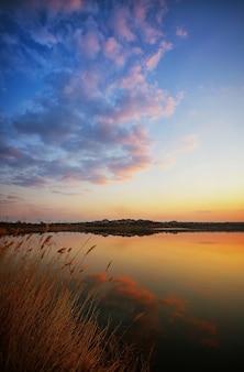 Schöner sonnenuntergang über dem see mit schönen abendwolken und wasserreflexion