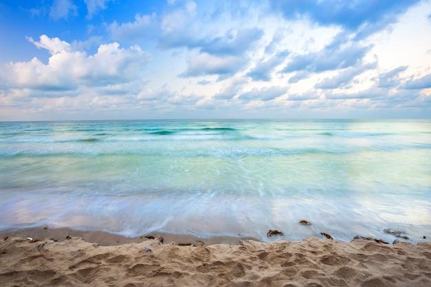 Schöner sonnenuntergang vorbei und welle des meeres auf dem sand setzen den horizont auf den strand