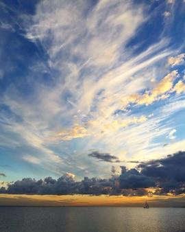 Schöner sonnenunterganghimmel auf dem meer oder see und bootssegelyacht bei sonnenuntergang schöne aussicht auf die natur