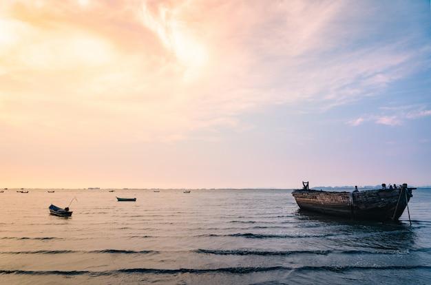 Schöner sonnenunterganghimmel und fischerboot auf dem meer