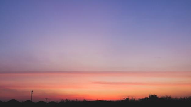 Schöner sonnenunterganglandschaftshintergrund im drastischen konzept. farbverlauf blau und orange klaren himmel ton und silhouette stadt.