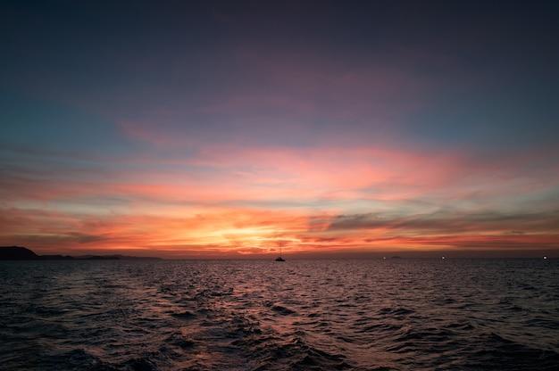Schöner sonnenuntergangshimmel über tropischem meer und bootssegeln am abend