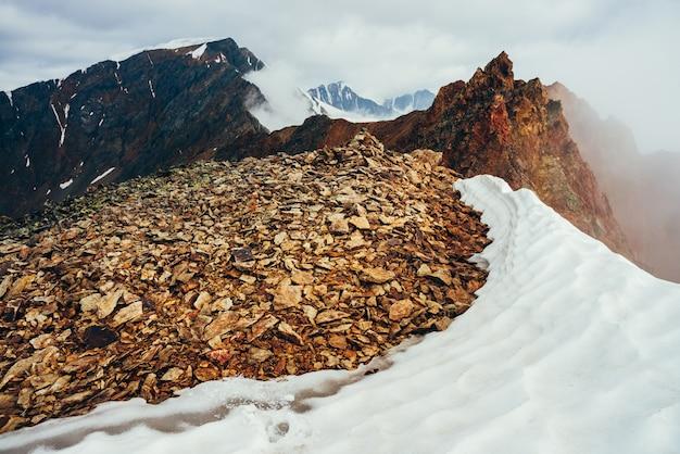 Schöner spitzer felsiger gipfel auf berg mit schnee unter dicken niedrigen wolken. atmosphärische minimalistische alpenlandschaft. scharfer felsiger berggipfel über dicken wolken im abgrund. wunderbare hochlandlandschaft.