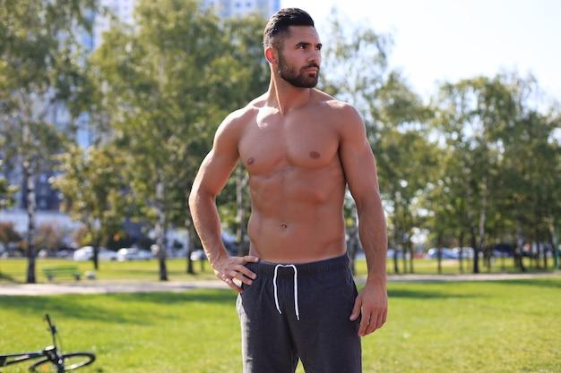 Schöner sportler mit nacktem oberkörper, der beim training am sonnigen tag im park ruht.