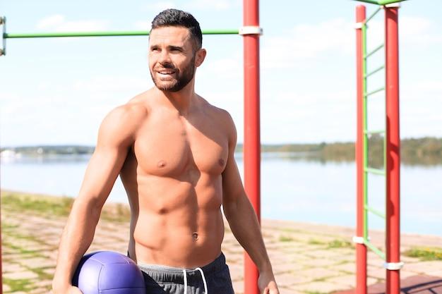 Schöner sportler mit nacktem oberkörper, der beim training mit fitnessball am sonnigen tag im park ruht.