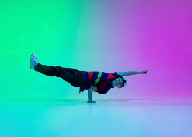 Schöner sportlicher junge tanzt hip-hop in stilvoller kleidung auf bunter farbverlaufswand im tanzsaal im neonlicht. jugendkultur, bewegung, stil und mode, action. modisches helles porträt.
