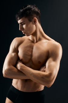 Schöner sportlicher mann mit muskulösem körper, der aufwirft