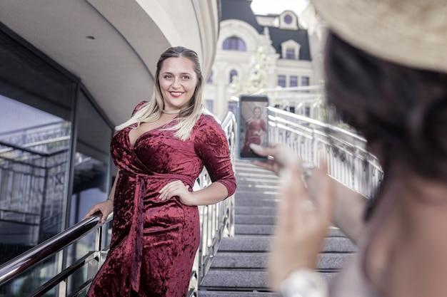 Schöner stil. freudige pralle frau, die ein rotes samtkleid trägt, während sie für ein foto aufwirft