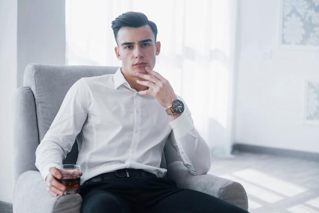 Schöner stil. junger eleganter kerl im weißen anzug sitzt auf dem stuhl und hält glas mit alkohol.