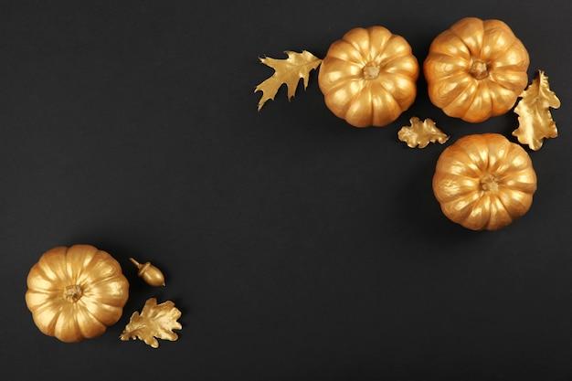 Schöner stilvoller herbsthintergrund mit draufsicht der goldenen blätter und der kürbise