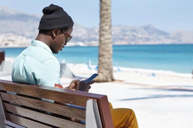 Schöner stilvoller junger mann, der ein elektronisches gerät an einem sonnigen tag verwendet