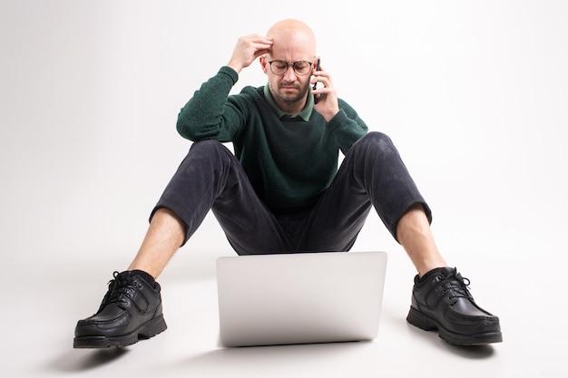 Schöner stilvoller nachdenklicher mann hält ein telefon, sitzt vor laptop, kommuniziert und arbeitet.