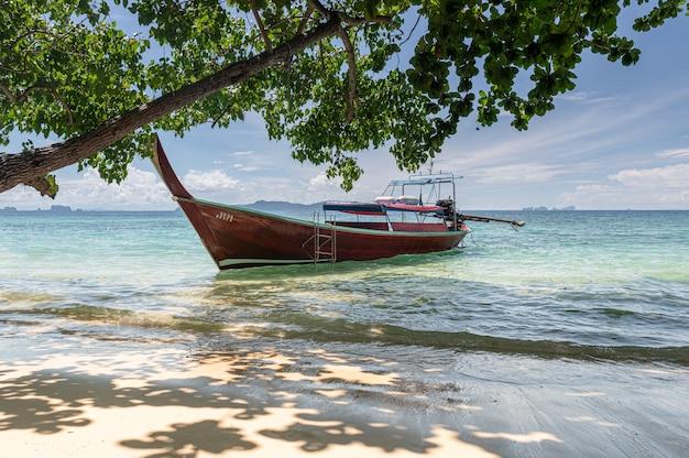 Schöner strand mit blauem wasser und boot