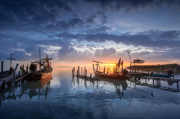 Schöner strand mit fischerboot während des sonnenaufgangs auf fischerdorf