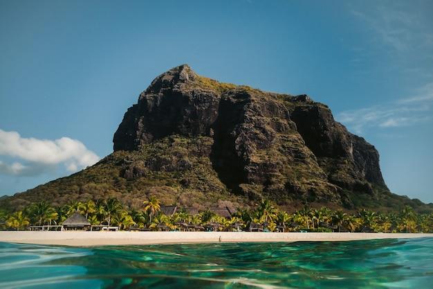Schöner strand, palmen und wolken am horizont. afrika, mauritius, süden, in der nähe von le morne.