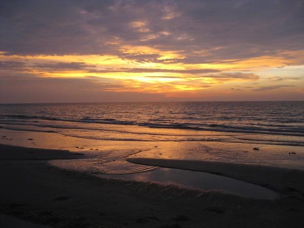 Schöner strand und das meer unter dem bunten himmel bei sonnenuntergang