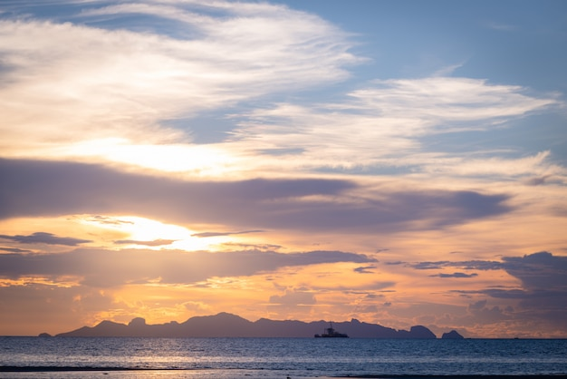 Schöner strandsonnenuntergang mit blauem meer und goldener heller himmelwolke