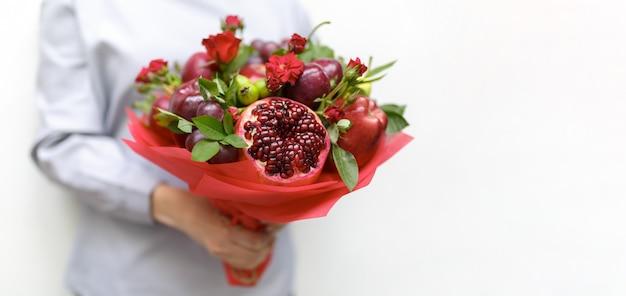 Schöner strauß bestehend aus granatapfel, äpfeln, trauben, pflaumen und scharlachroten rosen in den händen einer frau auf einem weiß als rohling für eine grußkarte