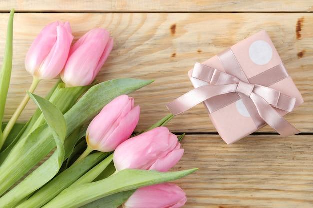 Schöner strauß der rosa tulpenblumen und der geschenkbox auf einer natürlichen holzoberfläche