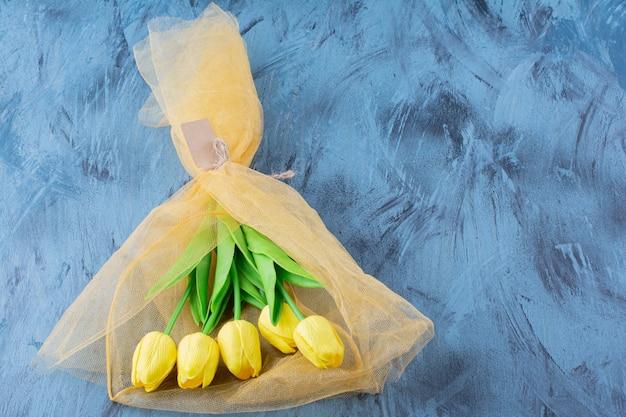Schöner strauß frischer gelber tulpen auf blau.