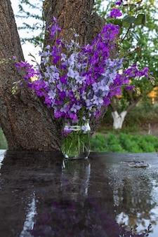 Schöner strauß hausblumen blau und lila rittersporn in einem glas wasser