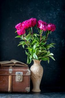 Schöner strauß roter pfingstrosen in einer tonvase in der nähe von altem koffer und buch, nahaufnahme