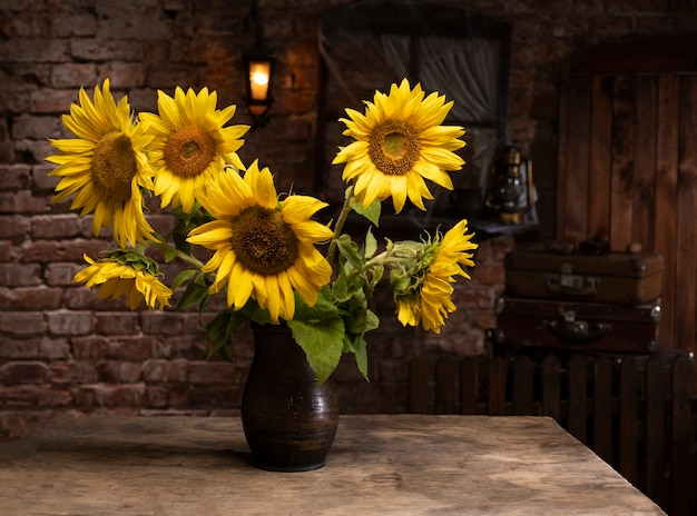 Schöner strauß sonnenblumen in vase auf einem holztisch. herbststillleben