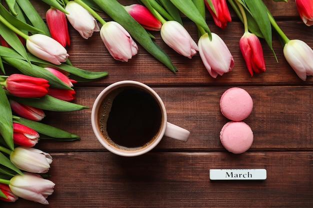 Schöner strauß tulpen tasse kaffee und acht geformte macarons
