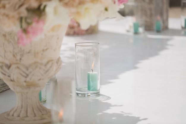 Schöner strauß von rosen in einer vase auf einem hintergrund eines hochzeitsbogens. wunderschönes setup für die hochzeitszeremonie.