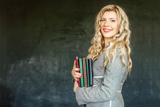 Schöner student mit büchern im klassenzimmer. konzept der erziehung