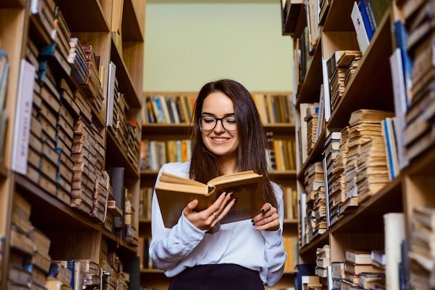 Schöner student steht in der bibliothek zwischen regalen voller bücher