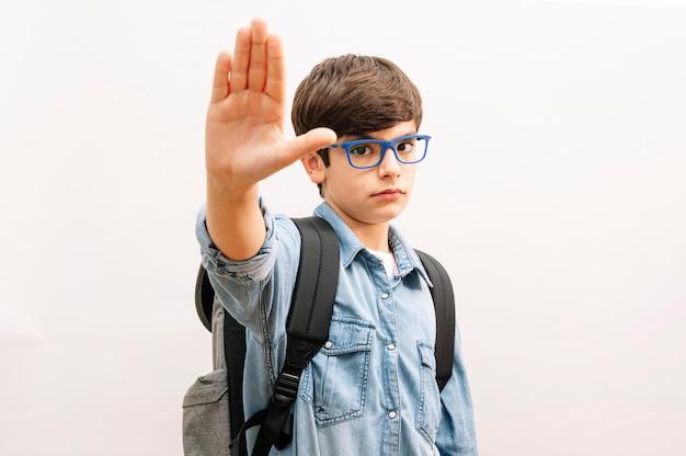 Schöner studentkindjunge, der rucksack hält bücher über lokalisierten weißen hintergrund mit offener hand tut stoppschild hält