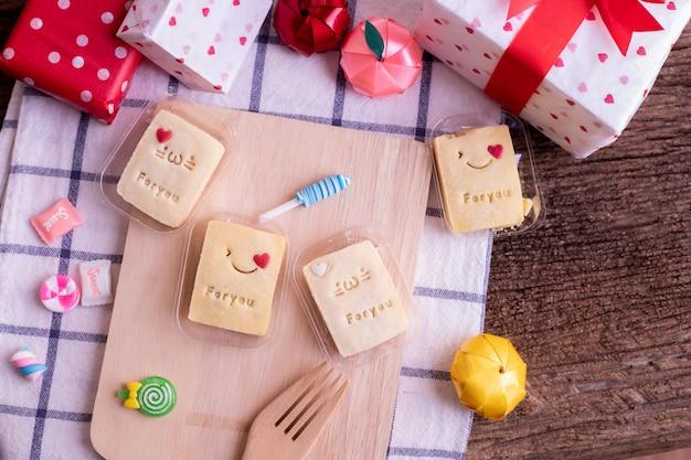 Schöner süßer nachtisch und geschenkbox auf hölzerner tabelle.