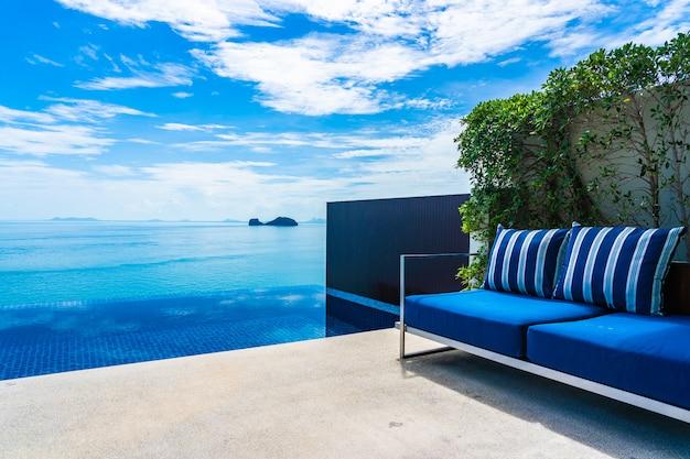 Schöner swimmingpool im freien mit seeozean auf blauem himmel der weißen wolke