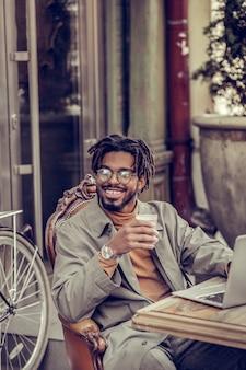 Schöner tag. erfreutes brünettes männchen, das lächeln auf seinem gesicht hält, während glas mit heißer schokolade hält