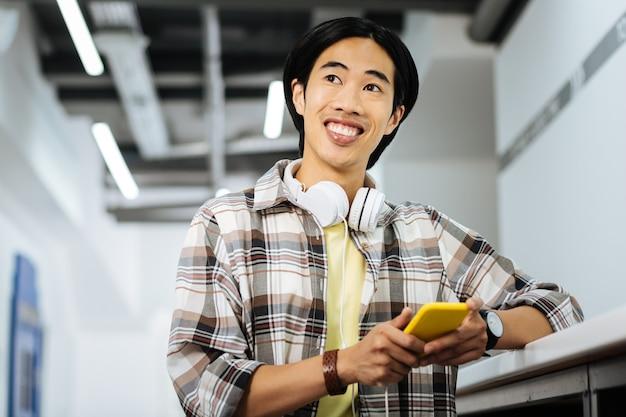 Schöner tag. fröhlicher emotionaler asiatischer student, der ein modernes gelbes smartphone hält und lächelt, während er in die ferne schaut und sich gut fühlt