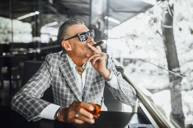 Schöner tag, geschäftsmann im anzug mit verdächtigem gesicht raucht