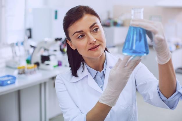 Schöner tag. inspirierter erfahrener wissenschaftler, der eine uniform trägt und eine röhre betrachtet