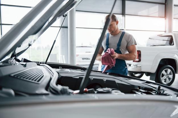 Schöner tag. mann in blauer uniform arbeitet mit kaputtem auto. reparaturen durchführen
