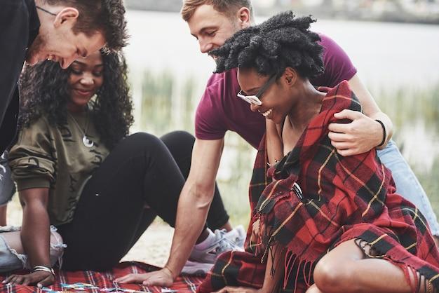 Schöner tag mit freunden. eine gruppe von menschen hat ein picknick am strand.