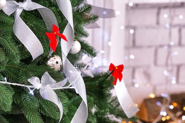 Schöner tannenbaum mit silbernen bändern und weihnachtsbeleuchtung im zimmer, nahaufnahme
