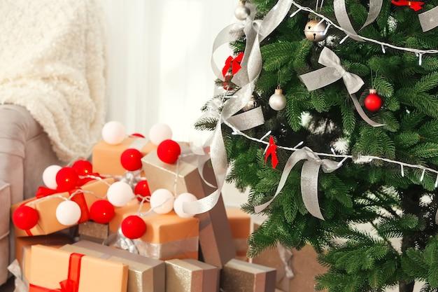 Schöner tannenbaum mit silbernen bändern und weihnachtsbeleuchtung im zimmer