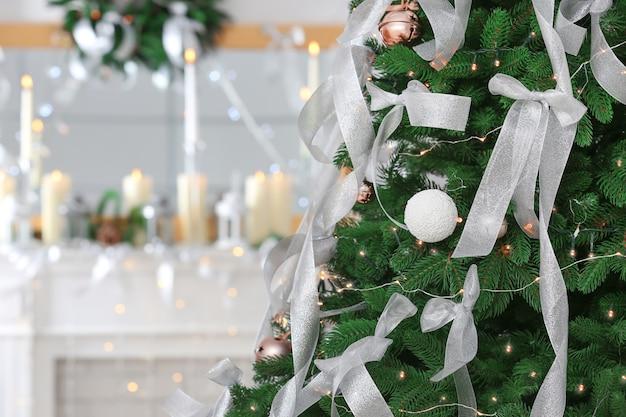 Schöner tannenbaum mit weihnachtsschmuck im zimmer