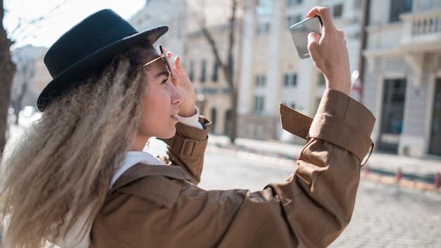 Schöner teenager mit dem lockigen haar, das ein foto macht