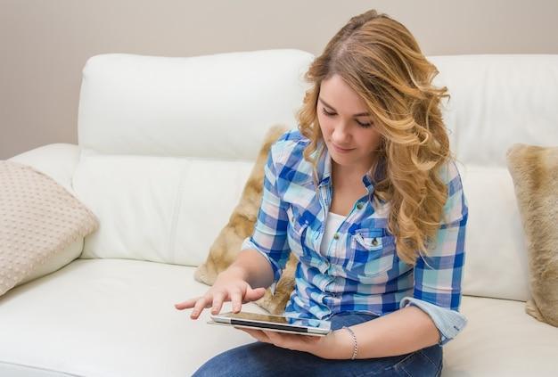Schöner teenager mit tablet-pc auf dem sofa sitzend