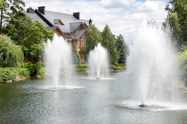 Schöner teich mit springbrunnen im luxuriösen herrenhaus