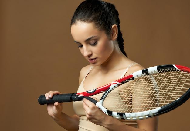 Schöner tennisspieler der jungen frau, der schläger hält