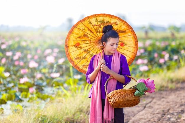 Schöner thailändischer frauenlandwirt, der thailändisches trachtenkleid trägt und auf den lotossee geht