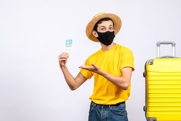 Schöner tourist der vorderansicht im gelben t-shirt, das nahe gelbem koffer steht, der reiseticket hält